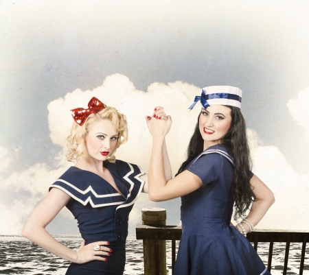 Vintage fashion fight. Beautiful young women with pinup hairstyle and makeup in an arm wrestle competition outdoors at a retro sea dock Stock Photo - 21577867