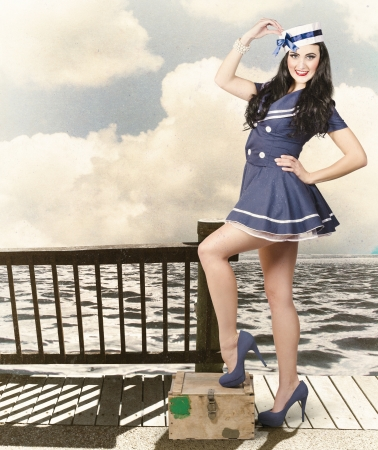 Vintage sailor girl beauty portrait. Woman in retro styled fashion posing on an ammunition weapon crate when on a world tour travel cruise Stock Photo - 21577868