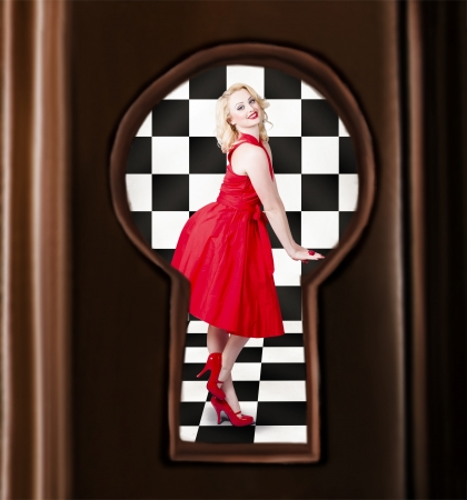 Retro fashion portrait of a stylish sensual pinup girl dancing in bright red dress. Image view through door keyhole photo