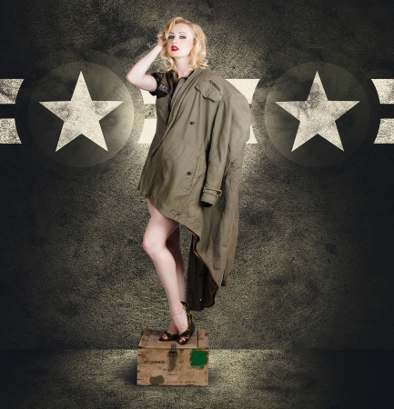 Vintage portrait of a beautiful young army pinup woman posing in military fashion with provocative style, camouflage heels and a military jacket on grunge star background photo