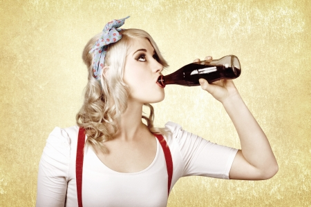 Beautiful blond pinup girl drinking soda drink at vintage sweets shop photo