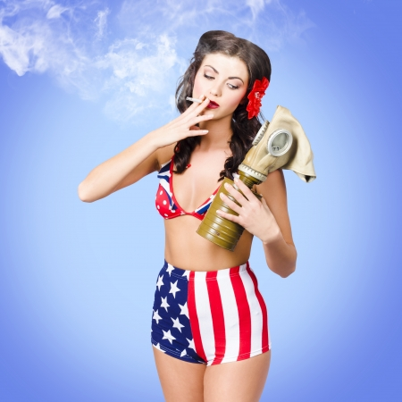Beautiful American army pin-up girl smoking cigarette while holding military issued gas mask on blue background photo