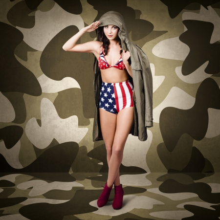 Retro pinup girl in army uniform standing in world war two camouflage interior with red boots photo