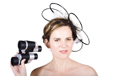 Isolated portrait of a beautiful woman watching horse races with binoculars on white background. Melbourne cup concept photo
