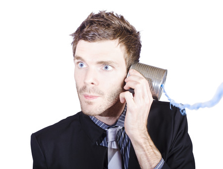 Young businessman listening to a conversation from a telephone can on white background photo
