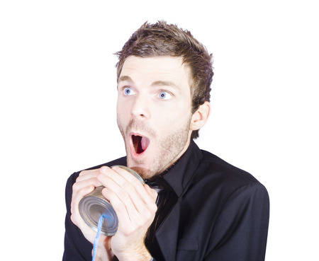 Funny sales man shouting out a sale pitch during a business conversation through a tin can phone Stock Photo - 22224666