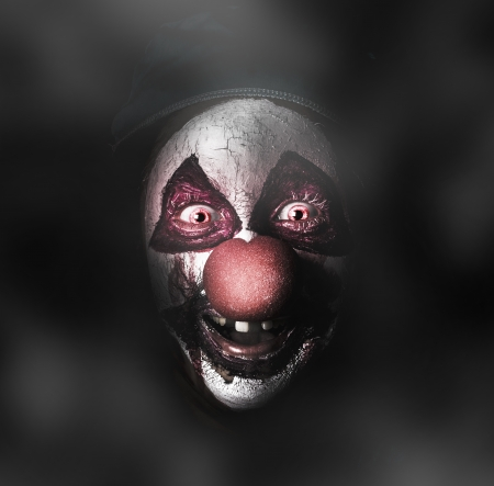 Dark carnival portrait on the face of an evil clown with a scary joker smile laughing in the black darkness. The Bogyman photo