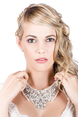 Portrait Of Gorgeous Blonde Bride Holding Precious Necklace photo