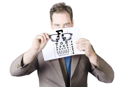 Mature Man In Suit Holding Spectacles In Front Of Eye Test Chart On White Background photo