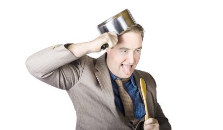 Nerdy Businessman With Tongue Out Holding Saucepan Overhead photo