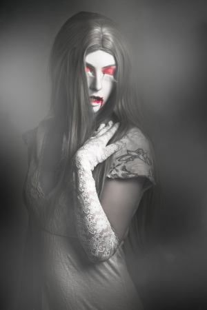 Dark fine art portrait of a beautiful vampire woman with long grey hair standing in a fog cover cemetery. Twilight nightmare  photo