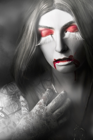 Halloween portrait of a beautiful young woman vampire with blood red lips wearing white lace dress reaching to silver necklace with expression of grief and loss Stock Photo - 22350705