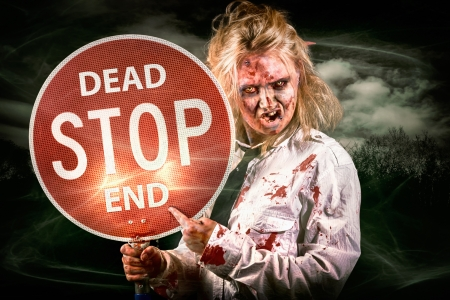 Halloween portrait of a scary zombie holding stop sign in a spooky field during night in a depiction of a dead end photo