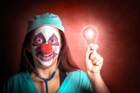 Portrait of a smiling clown doctor holding red emergency light bulb Stock Photo - 22399622