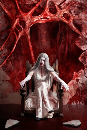 Halloween fine art portrait of a beautiful young woman dressed as dark vampire in messy white dress seated at the entrance to hell  photo