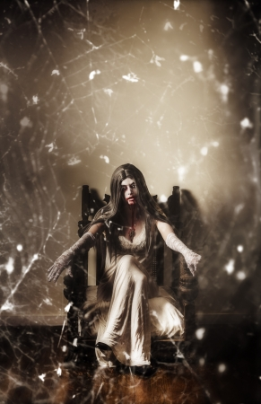 Dark portrait of a possessed demon woman  seated in haunted house in vintage fashion with spiderweb. Devil is in the details photo