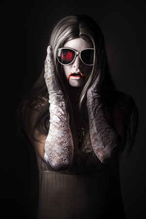 Fantasy portrait of a gothic vampire woman wearing blood splattered sunglasses when hiding from the light Stock Photo - 22611616