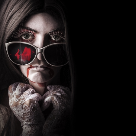 Horror fashion model wearing bloody sunglasses with gothic lace gloves and white face makeup. Vampire beauty in the darkness photo