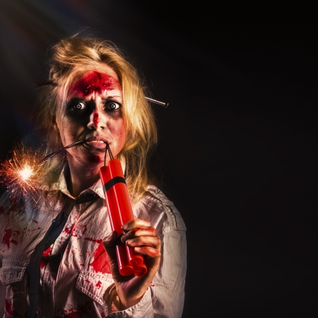 Evil female halloween zombie with bloody face holding bomb on creepy dark background. Attack of the dead photo