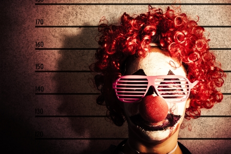 Grunge portrait of a funny clown criminal getting mug shot ID photo on police lines photo