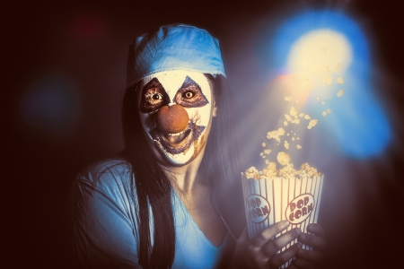 Scary zombie clown holding popcorn in cinema while watching a halloween horror movie. Slasher movies at the THEATER concept photo