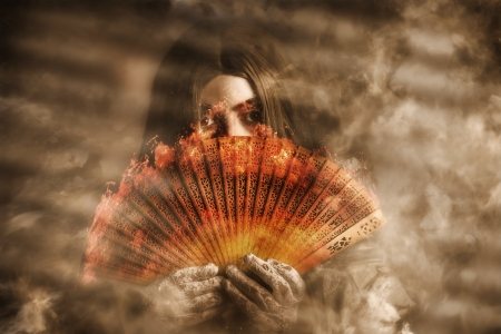 Mystic fire woman holding a burning oriental fan in a smokey haze of mystery and magic. psychic Clairvoyant Stock Photo - 23263418