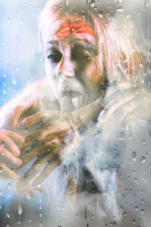 Scary halloween scene of a horror zombie licking on a human hand in front of a wet glass window pane photo