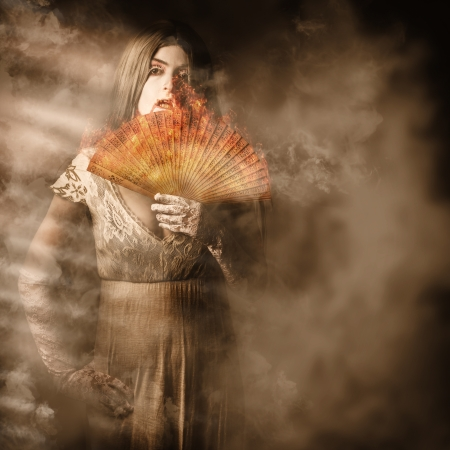 Old fantasy fine art portrait of an elegant vampire woman holding hand fan engulfed in fire amongst a mist of smoke and atmosphere photo