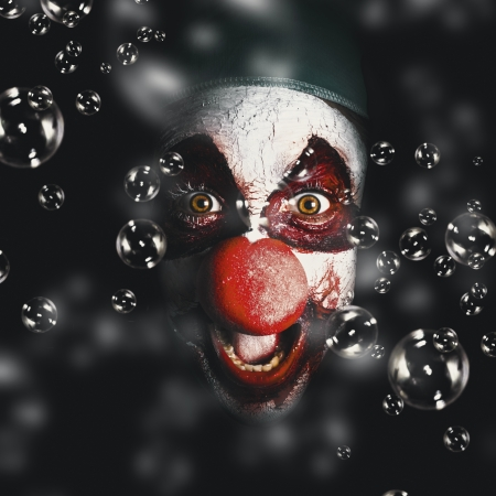Closeup portrait on a scary horror circus clown laughing with evil smile among birthday party bubbles. Crazy celebration photo