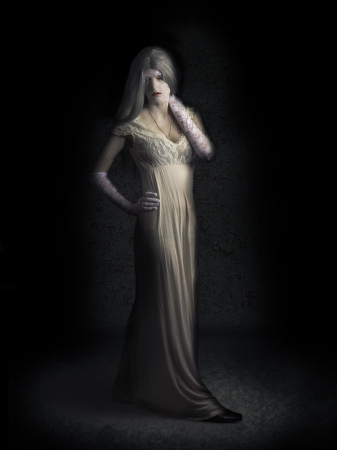 Scary vampire woman in vintage full length white wedding dress posing with cracked skin and ghoulish eyes in shadow lair. Queen of the damned photo