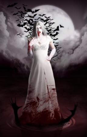 Halloween scene of an immortal female vampire standing in full length in a bloody white dress in a slaughter pool with drowning corpse  photo