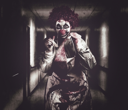 Madness the creepy medical clown standing in grunge hospital hallway with flashlight and tongue prong. Terminal treatment photo