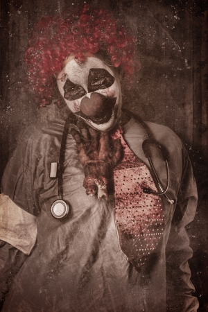 Funny portrait of an evil vintage clown doctor getting chocked by a chopped off hand inside autopsy clinic. Revenge attack photo