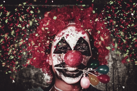 Horizontal close-up portrait on the face of a mad carnival clown holding balloon cake decoration in mouth under a fall of confetti. Celebrating Halloween photo