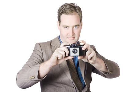 Isolated image of a man taking picture with 1950s film camera over white background. Fifties crime scene photographer photo