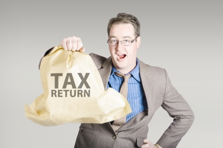 Business man holding income tax return with a happy expression of surprise. Big refund concept photo