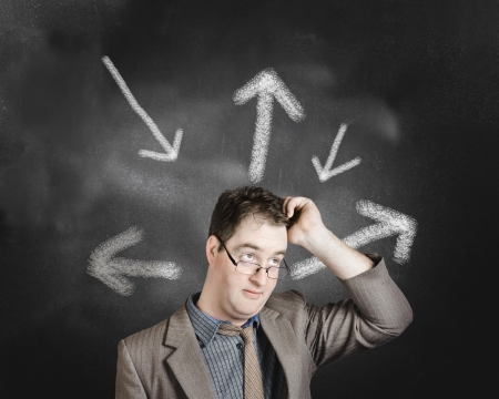 Businessman with multiple choices thinking up a direction forward on arrow chalkboard background. Career path strategy  photo