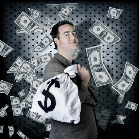 Business man stowing away cash inside bank vault when hording away finance money bag with greedy expression photo