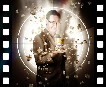 Movie poster concept of a man holding cinema popcorn bucket with falling kernels standing in front of film screen. Reel entertainment photo