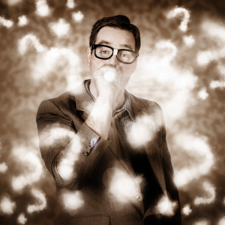 Creative design photograph of a businessman thinking with search light in a cloudy haze of question marks. Problem solving photo