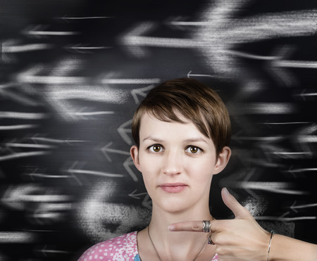 Young woman pointing on chalkboard arrow background. Business career directions in motion photo