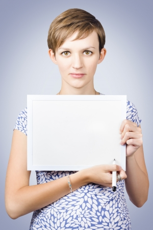 Serious woman holding white board with marker pen when writing Informative communication on blue studio background photo