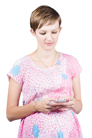 Isolated portrait of a pregnant woman texting on smart mobile phone over white background photo