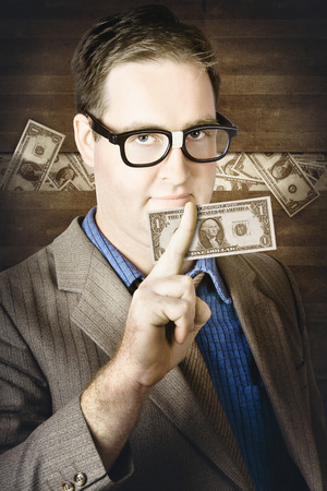 Banking business man standing in front of a concealment of stashed money holding American one dollar note in a depiction of personal wealth and finance photo