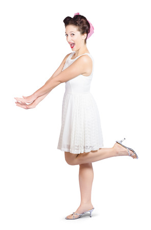 Full body portrait of a surprised housewife kicking up leg in white dress and checker bandana, over white background photo
