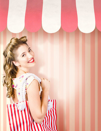 Beauty and fashion portrait of a beautiful blond woman with pinup hair style carrying shopping bag on pink stripe salon wall. Cosmetic and hairdresser copyspace photo