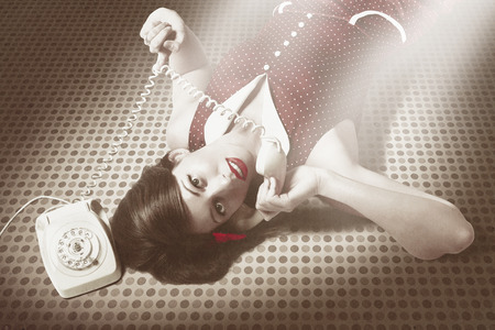 Vintage portrait of a beautiful brunette pinup woman with red lips and selenium toned dress talking on antique telephone against polka dot background. Hot line secretary  Stock Photo - 30532033