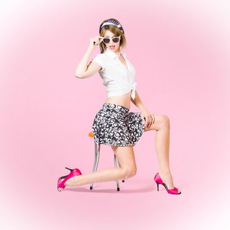 Pink pop art photo of a beautiful pinup girl strutting a beauty pose wearing 1950 style mini skirt and tied shirt with pink high heel shoes and girly accessories. Makeup and hairstyle concept Stock Photo - 30532035