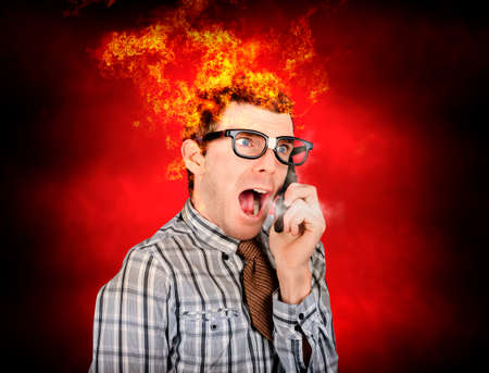 heaving: Funny portrait of a angry business man heaving heavy breaths of smoke with head engulfed in fire on mobile phone. Heated exchange Stock Photo