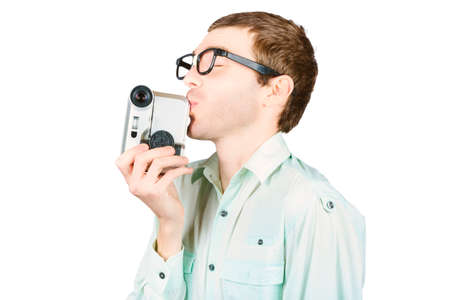 love movies: Nerdy man making romantic comedy movies when kissing digital video recorder. Movie love Stock Photo